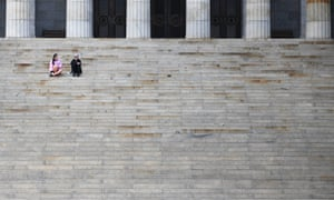 People are seen sitting on the staircase at the Shrine of Remembrance in Melbourne