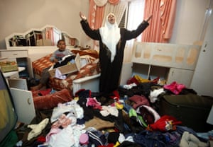 Hebron, West Bank: A woman and child stand amid their belongings after a raid by the Israeli army