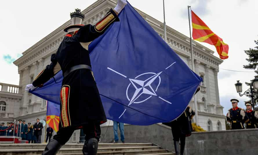Members of an honour guard hoist the Nato flag in front of the government building in Skopje