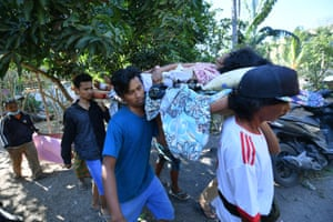 Local people carry an injured woman in Pemenang, North Lombok.