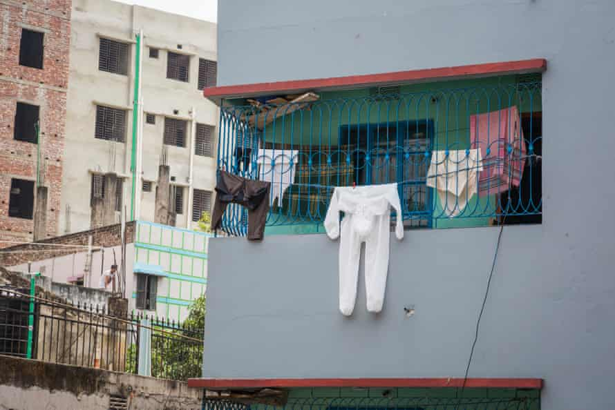 A white protective suit is among the laundry hanging from the veranda of an apartment belonging to a neighbour of the photographer