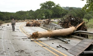 A DPS Trooper walks along the Highway 12 bridge over the Blanco River in Wimberley which was blocked by large trees after the flooding.