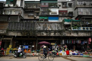 Hanoi, Vietnam. A woman rides her bike past shops beneath a residential building