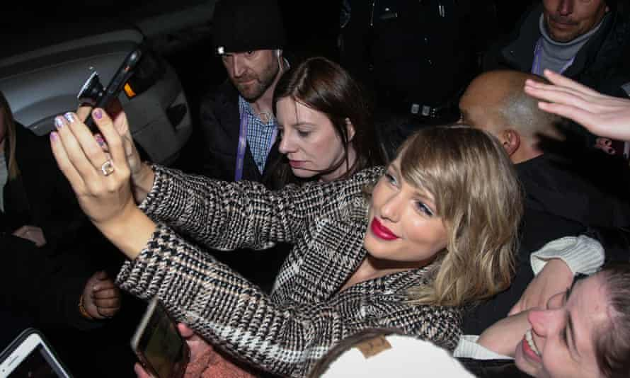 Taylor Swift takes selfies with fans before the Miss Americana premiere.