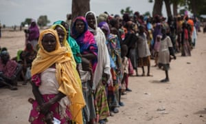 Women and children queue outside a Unicef nutrition clinic in a makeshift settlement in Muna, Maiduguri