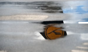 """The tail unit of a parked airplane of the German airline Lufthansa reflects in a puddle at the """"Franz-Josef-Strauss"""" airport in Munich, southern Germany, on June 11, 2020."""