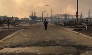 A Royal Canadian Mounted Police walking along a fire devastated street in Fort McMurray, Alberta, Canada.