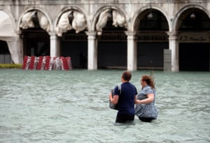 A couple walk in the flooded Saint Mark Square during a period of seasonal high water in Venice