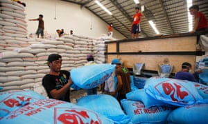 Filipino workers prepare for the distribution of aid at a relief centre