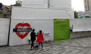 Women walk past a hoarding covered in messages of condolence at the base of Grenfell Tower