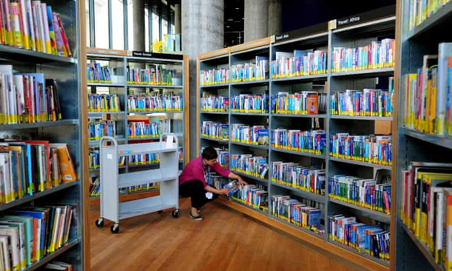 A librarian files books in a public library