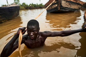 A Malian pulls his boat to a site where he can dive and collect sand from the riverbed near Kangaba