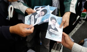 Iranian campaign workers distribute electoral posters Ebrahim Raisi.