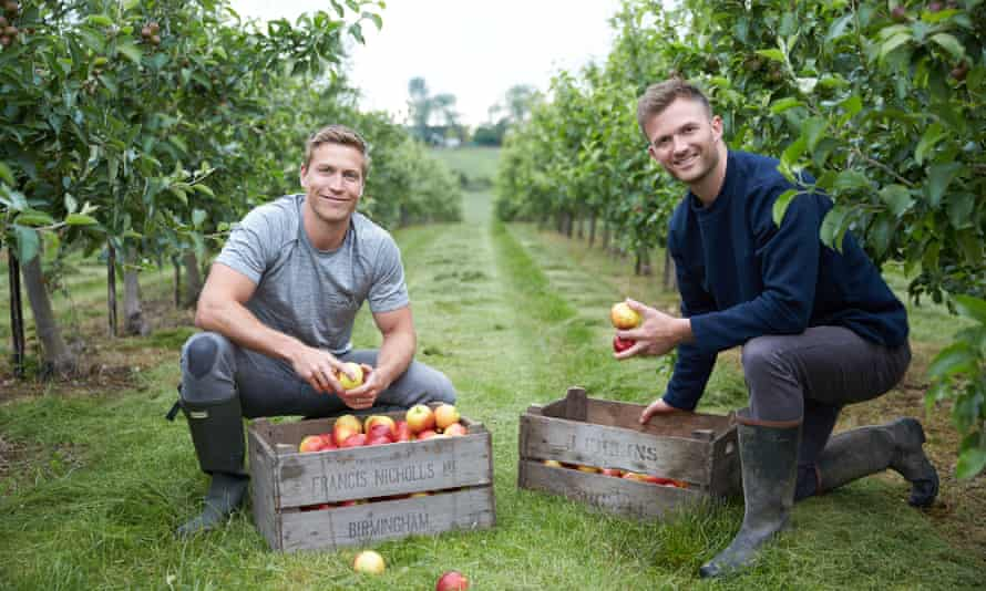 Myles Hopper and Giles Humphries crouching by a box of apples in an orchard