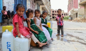 Displaced Yemeni children from Hodeida province sit on water containers in a street in Taiz