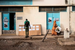 Dakar, Senegal: a high school student at the Lycee Blaise Diagne checks a list to find the location of his classroom on the first day back at school, while a teacher puts up coronavirus awareness posters in Dakar
