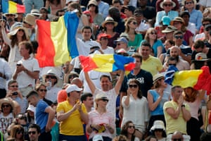 Spectators hold Romanian flags