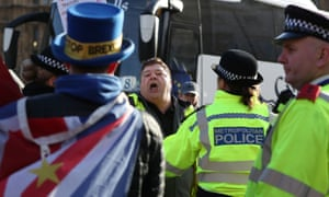 A leave supporter is held back by police as he argues with a remain supporter outside parliament in London.