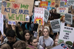Protesters hold signs at the YouthStrike4Climate student march in London.