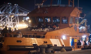 People rescued off Gibraltar prepare to spend the night onboard a Spanish rescue boat at the port of Algeciras, Spain.