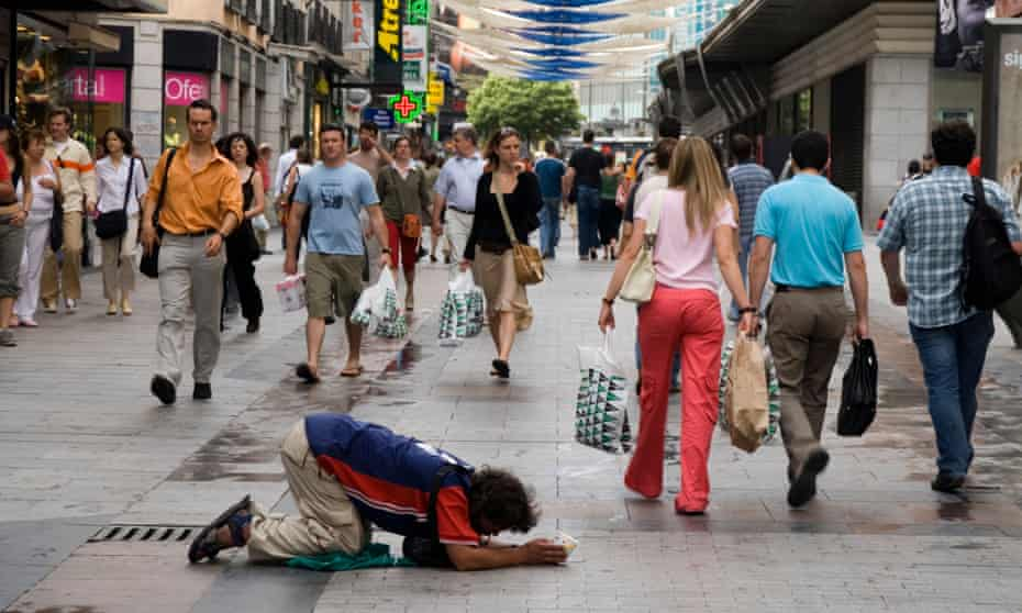 A man begs for money in Madrid Spain.