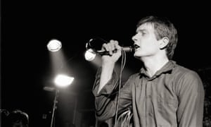 Ian Curtis performing live onstage at a Joy Division concert.