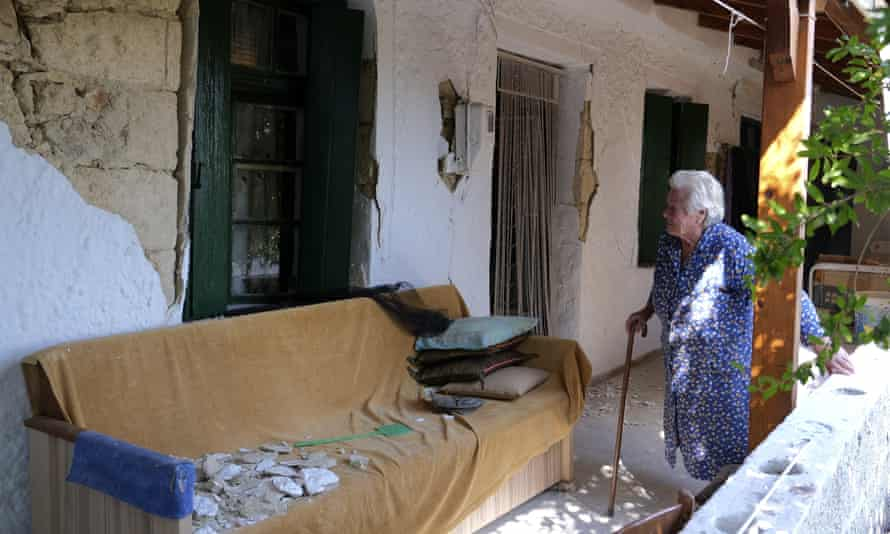 A woman looks at her damaged house in Archontiko village on Crete, Greece, on 28 September after an earthquake struck the day before.