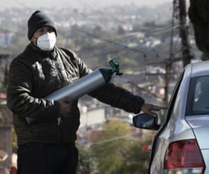 Ricardo Ledesma Carrasco gets into his car after filling an oxygen tank at a store for his father who is being treated for Covid-19 at his home in Mexico City.  Carrasco's mother also has Covid-19.