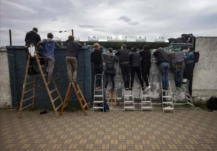 Bohemians' supporters watch the match between Bohemians 1905 and SK Dynamo Ceske Budejovice behind a wall amid the new coronavirus restrictions in Prague on 31 May.
