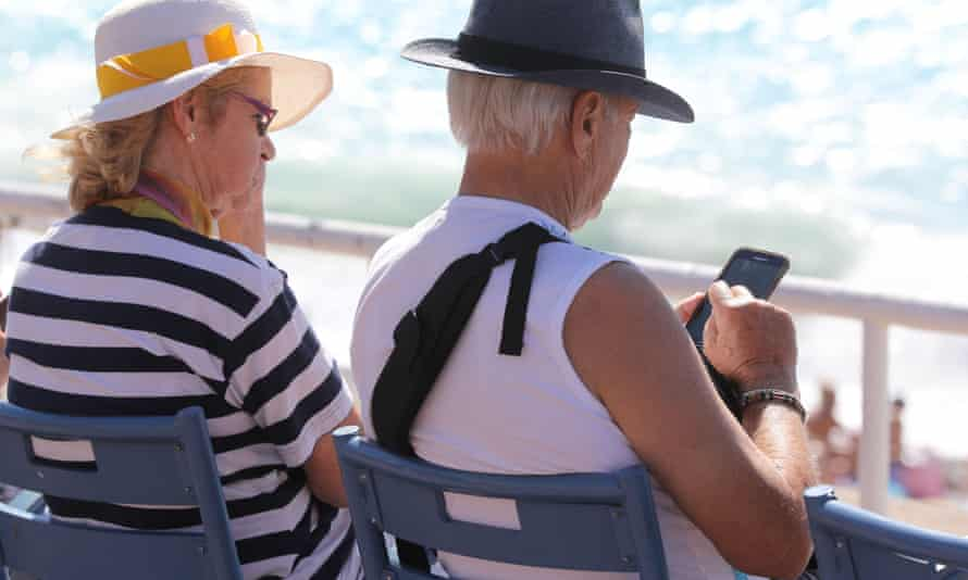 A man using a mobile phone while sitting beside a companion on the Promenades des Anglais beachfront in the French riviera city of Nice.