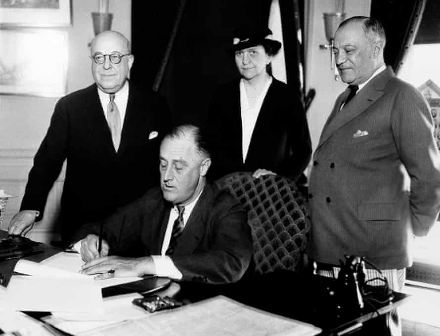 Franklin D Roosevelt signs a bill at the White House in 1933, with Frances Perkins behind him.