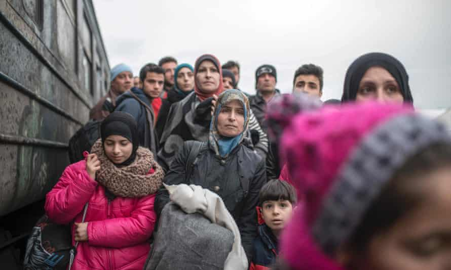 Migrants and refugees board a train heading to Serbia from the Macedonian-Greek border