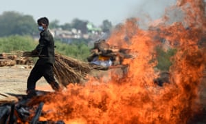 A worker walks past the burning funeral pyre of a Covid victim at a cremation site in Allahabad, India