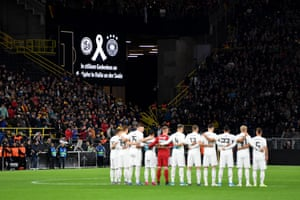 Players, officials and fans take part in a minutes silence.