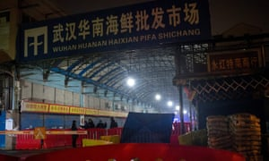 This photo taken on January 11, 2020 shows security guards standing in front of the closed Huanan Seafood Wholesale Market in the city of Wuhan, in central China's Hubei province.