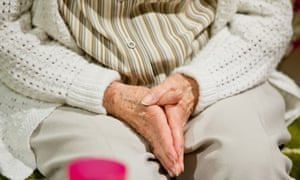 A woman with dementia clasps her hands together