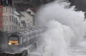 Dawlish, England Large waves crash over a train as it passes through