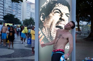 An Argentinian fan poses in front of an Adidas advert pretending to be bitten by Luis Suarez at Copacabana Beach in Rio de Janeiro in June 2014.
