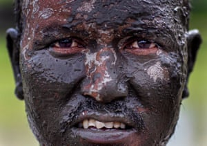 A farmer's face is covered in mud
