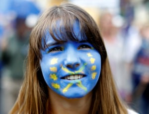 A woman wears face paint in the colours of the European flag.