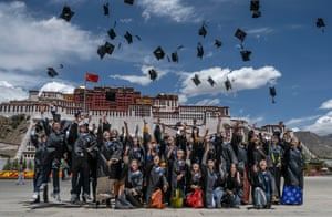 Tibetan University graduates throw their hats in the air as they have their photos taken in front of the Potala Palace, a UNESCO heritage site, after graduation