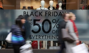 Shoppers pass a promotional sign for Black Friday sales discounts on Oxford Street in London.