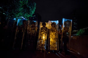 Police carry riot shields during clashes after a rally against the proposed extradition bill