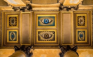 Colin Gill 1928 North Portico ceiling, Blenheim Palace Oxford. Six unblinking, disembodied eyes bear down on all those who arrive at the principal entrance to the palatial setting of BlenheimPalace, the ancestral home of Sir Winston Churchill. Three eye sare brown, the remaining three a cerulean blue, all of them encased in enigmatic starbursts. It is a peculiar welcome to one of England's largest and most prestigious stately homes, the only secular and non-royal building in the country to be known asa 'palace'.