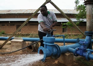 David Kasikila, the man who led the Kasongo water rehabilitation project to fruition, turns on the tap on the extended system.