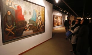 Visitors look at a painting by the Iranian artist Kazem Chalipa at the opening of the show.
