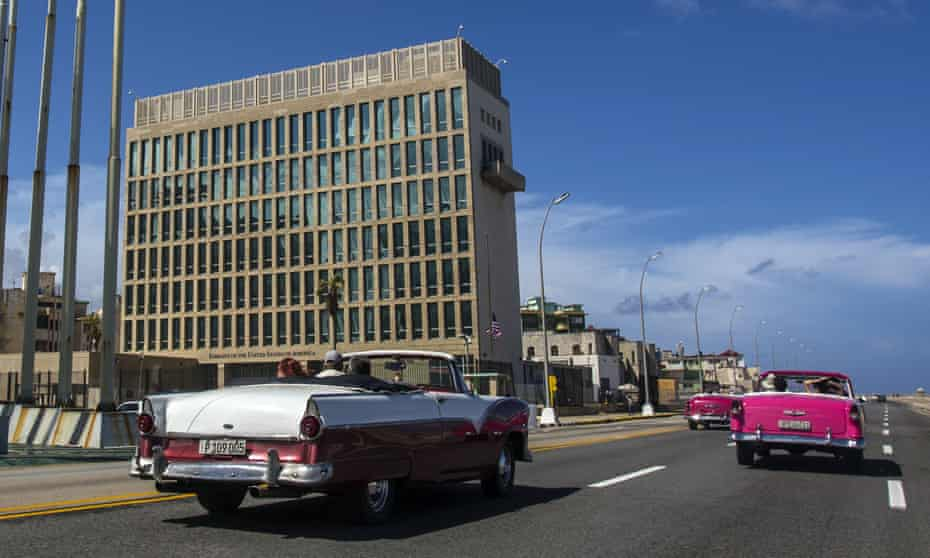 Tourists ride classic convertible cars on the Malecón beside the US embassy in Havana, Cuba.