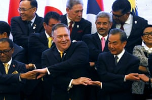 The US secretary of state, Mike Pompeo, performs the traditional 'ASEAN handshake' with the Chinese foreign minister, Wang Yi, in Bangkok, Thailand