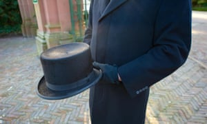 a funeral director holds his top hat
