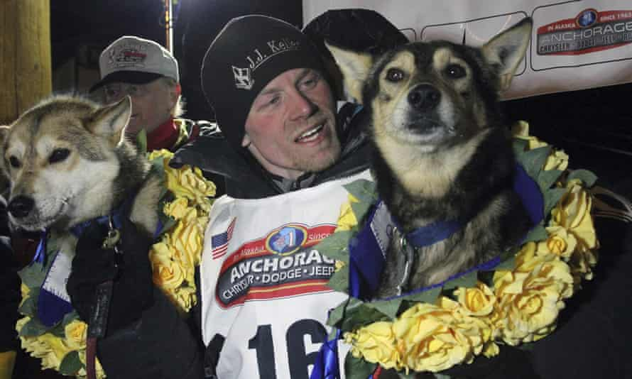 Dallas Seavey poses with his lead dogs Reef, left, and Tide after winning the Iditarod Trail sled dog race in Nome, Alaska, in 2016.